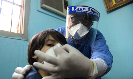 An Egyptian doctor adjusts the protective mask covering a young patient