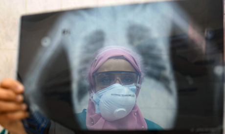 An Egyptian doctor wearing two protective masks checks a patient