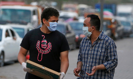 Men wearing face masks walk along a street before curfew, during the global outbreak of the coronavi