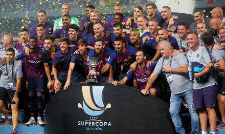 FILE PHOTO: August 12, 2018 Barcelona celebrate winning the Spanish Super Cup with the trophy (Reute