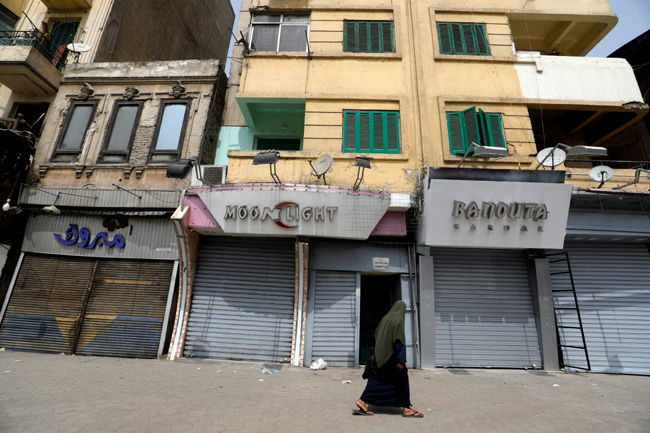 FILE PHOTO: A woman walks past a closed shop following the spread of coronavirus disease (COVID-19),