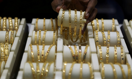 FILE PHOTO: A salesman arranges gold bangles inside a jewellery showroom on the occasion of Akshaya