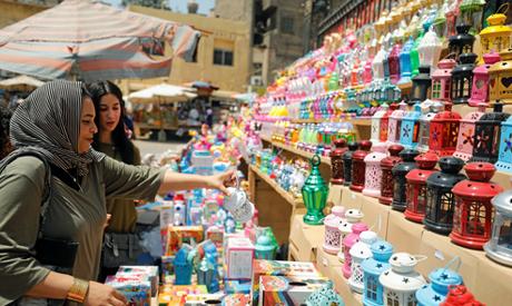 "An Egyptian woman checks traditional Ramadan lantern called ""fanous"" at a shop stall ahead of the Mu"