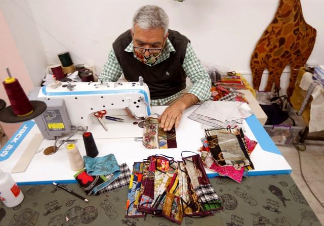 A worker sews silk face masks
