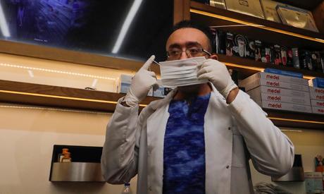 "Dr. Wael Abd Elaziz wears a protective mask in ""Dawa Pharmacy"" the first Egyptian pharmacy using a r"