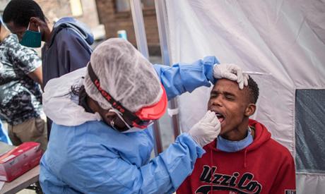Doctors Without Border (MSF) nurse Bhelekazi Mdlalose (C) performs a COVID-19 coronavirus test durin