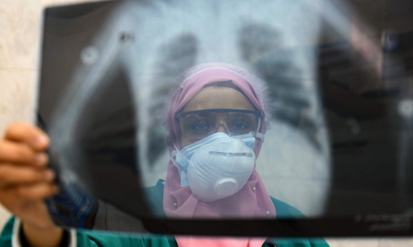 [ile photo taken on April 19, 2020, an Egyptian doctor wearing two protective masks checks a patient