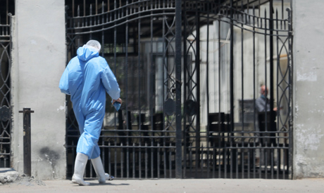 A member of medical team wearing protective equipment enters the Institute of Research for Tropical