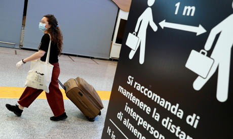 A passenger wearing a protective face mask passes near a sign indicating to keep the social distanci