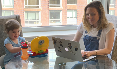 In this May 15, 2020 image, Blake Ross, founder of Kindness of Strangers, right, works on her laptop