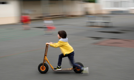 A child rides a scooter in a courtyard of a private school open to children of health workers and wo