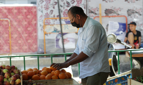 A man buys fruits from a cafe transformed into a fruit and vegetable shop, as cafes have been closed