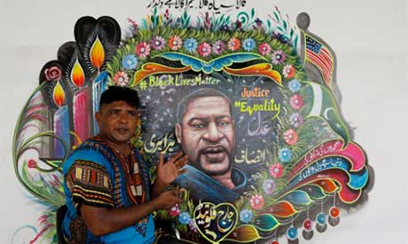 Haider Ali next to a mural he painted, depicting George Floyd