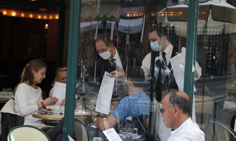 Waiters present the menu to customers at The Select restaurant, in Paris, Montparnasse district, Mon