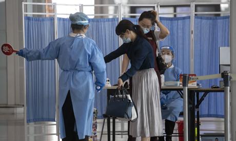 Health workers screen visitors to the Beijing Capital Airport terminal 3 departure hall in Beijing