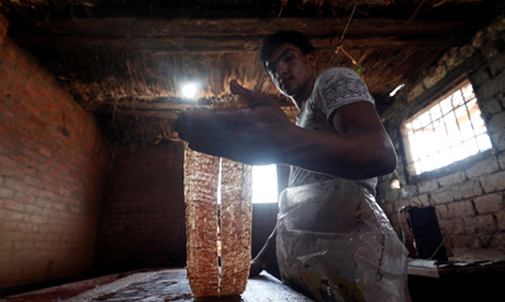 Mohamed Abdul Rahman, 18, son of a papyrus farmlands and workshops owner prepares a papyrus sheet be