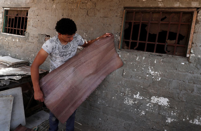 Mohamed Abdul Rahman, 18, son of a papyrus farmlands and workshops owner checks sheets if the papyru