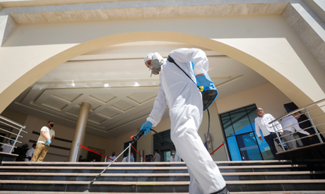 A worker wearing a protective gear disinfects the stairs of the Albatros White Beach Resort, amid th