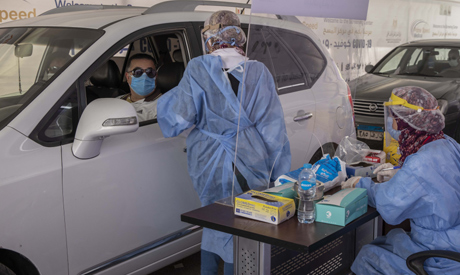 A health worker wearing protective gear prepares to take swab samples from people queuing in their c