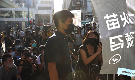 Hong Kong activist Joshua Wong, center, and Jannelle Rosalynne Leung announce their plan to run for