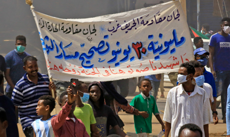 """Sudanese demonstrators lift a banner which reads """"June 30"""
