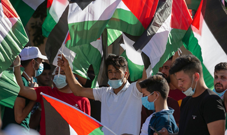 File photo: Palestinians wave national flags as they attend a rally against Israel's West Bank annex