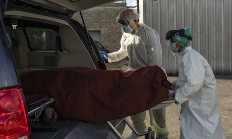 HOUSTON, TX - JUNE 30: Medical staff wearing full PPE push a stretcher with a deceased patient into