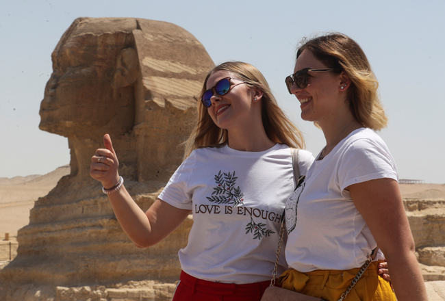 Women pose in front of Sphinx at the Great Pyramids of Giza after reopening for tourist visits, foll