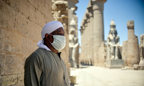 A mask-clad local caretaker looks on as visitors arrive at the ancient Temple of Luxor in Egypt