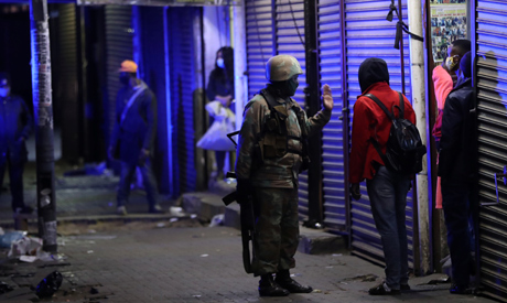 A member of the South African military talks to a man during a patrol as a nighttime curfew is reimp