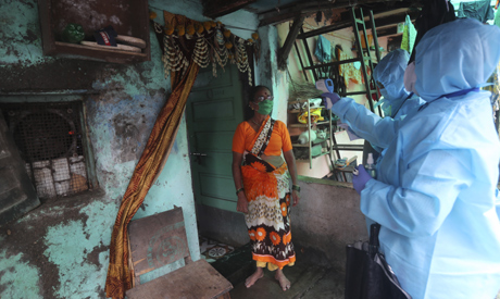 Health workers screen people for COVID-19 symptoms at a slum in Mumbai, India, Tuesday, July 14, 202