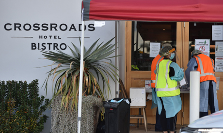 Medical workers are seen at a COVID-19 coronavirus testing station at the Crossroads Hotel, a popula