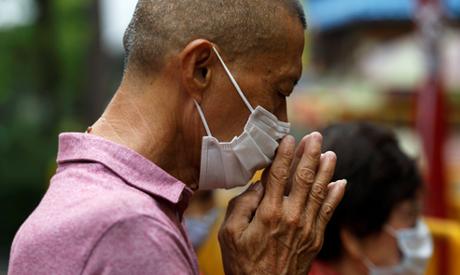man wearing a protective face mask prays outside a temple, amid the coronavirus disease (COVID-19) o