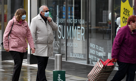 Pedestrians, some wearing a face mask or covering due to the COVID-19 pandemic, walk past an electro