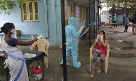 A woman gets her nasal swab sample taken to test for the coronavirus at a government health center i