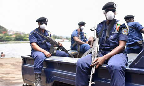 FILE PHOTO: Congolese policemen wear masks as they ride on their patrol pick-up truck amid the coron