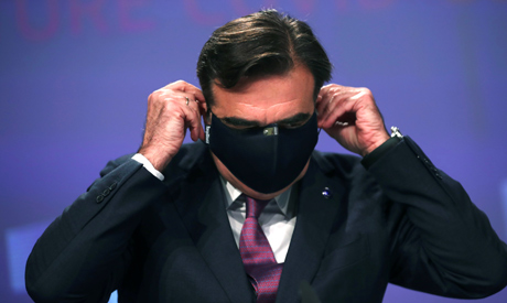 European Commission Vice-President Margaritis Schinas puts his protective mask on after addressing a