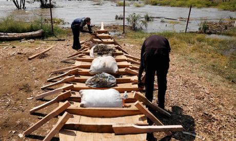 Men construct a fishing boat on a beach at Lake Turkana, near the town of Kalokol, Turkana county, K
