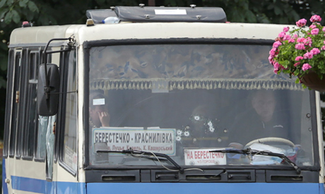 Hostages are seen through a windscreen damaged by weapon shots, after a passenger bus was seized by