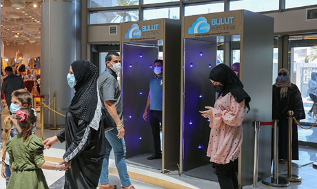 Iraqis wearing protective masks walk into a disinfection booth while entering the Mall of Baghdad as