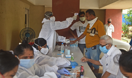 A medical volunteer wearing protective gear takes temperature reading of a man during a medical scre