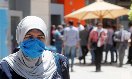A woman wearing a protective mask looks on as people wait to make withdrawals outside a bank in Cair