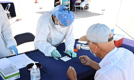 A person undergoes a finger prick blood sample as part of a coronavirus antibody rapid serological t