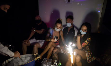 People wearing face masks to prevent the spread of coronavirus gather in a discotheque in Madrid, Sp