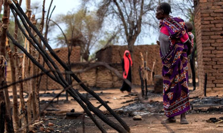 A woman looks at burnt houses during clashes between nomads and residents in Deleij village, located