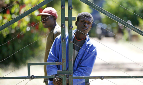 File photograph taken on April 17, 2009, two men stand by the gates of a farm which they seized from