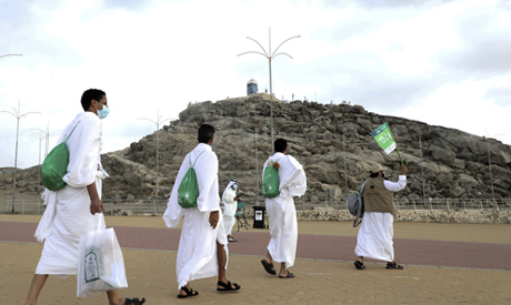 Muslim pilgrims walks towards the rocky hill known as Mountain of Mercy, at back ground, on the Plai