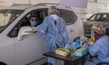 File photo, a health worker prepares to take swab samples to test for the coronavirus at a drive-thr