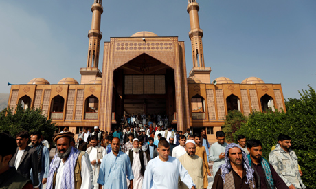 Afghan men leave a mosque after prayers during the Muslim festival of Eid al-Adha, amid the spread o