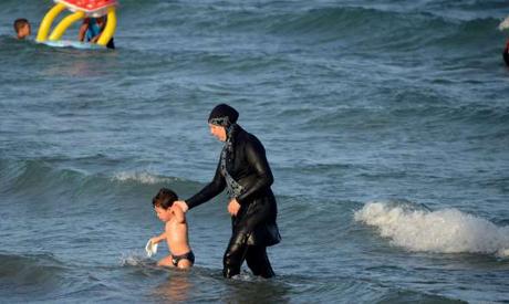 "File photo: A Tunisian woman wearing a ""burkini"" a full-body swimsuit designed for Muslim women, wal"